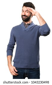 Handsome brunette man with beard saluting on white background