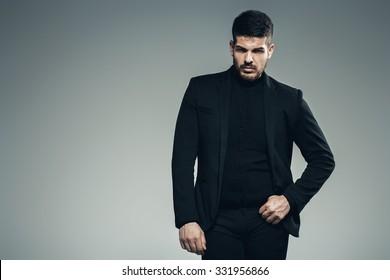 handsome brunette man in black jacket and pants in studio