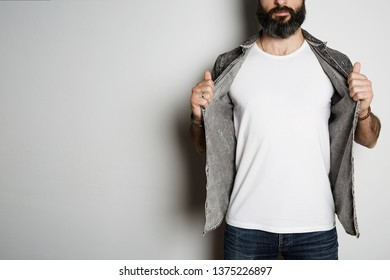 Handsome brutal bearded hipster model poses in black jeans shirt and blank white t-shirt premium summer cotton, on white background. Copy paste Advertisement