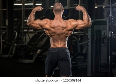 Handsome brutal caucasian strong young muscle man model appearance workout training pumping up back muscles lats in gym fitness bodybuilding and sport nutrition