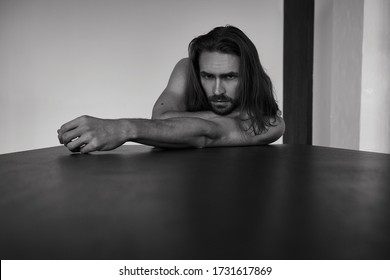 Handsome brutal man with beard and cool long hair.Sexy topless athletic body. Confident, attractive, stylish. Fashion shooting. Actor. Black and white - Shutterstock ID 1731617869