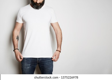 Handsome brutal tattooed bearded guy poses in blue jeans and blank gray t-shirt premium summer cotton, on white background. Mockup Copy Paste Advertisement