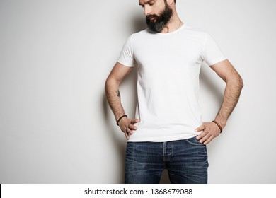 Handsome brutal tattooed bearded male model poses in blue jeans and blank white t-shirt premium summer cotton, on white background