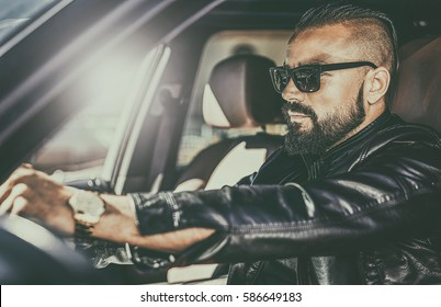 Handsome brutal young man behind the wheel of a luxury car