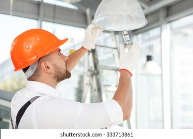 Handsome builder is screwing an electric light bulb into a fixture. He is standing and looking up with concentration