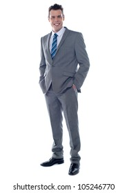 Handsome business executive posing with hands in pocket. Full length portrait