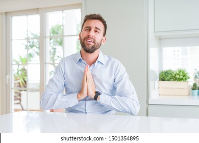 Handsome business man begging and praying with hands together with hope expression on face very emotional and worried. Asking for forgiveness. Religion concept.