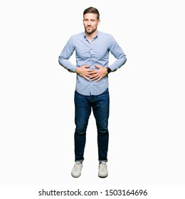 Handsome business man with blue eyes with hand on stomach because indigestion, painful illness feeling unwell. Ache concept.