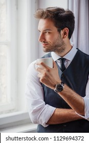 Handsome business man enjoying his morning cup of coffee, getting ready for work, enjoying city view from a window