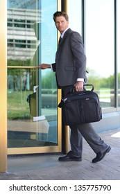 Handsome Business Man Entering Building through Revolving Doors