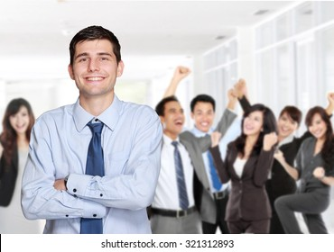 handsome business man in front of his team member celebrating their achievement