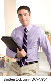 A handsome business man holding a leather folio, leaning on desk.