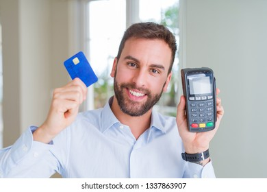 Handsome business man holding pos terminal and credit card, buying and payment using dataphone