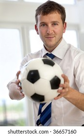 Handsome business man indoors holding a football