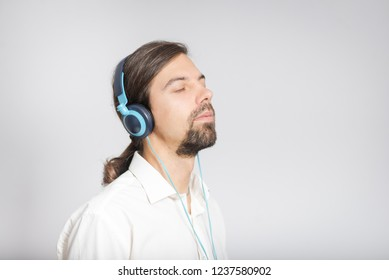 handsome business man listening to music with headphones, long haired isolated on background