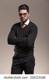 Handsome business man looking at the camera holding his arms crossed. On grey background.