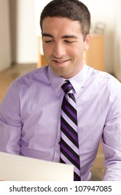 Handsome business man looking at a piece of paper wearing a purple shirt and tie in an office setting.