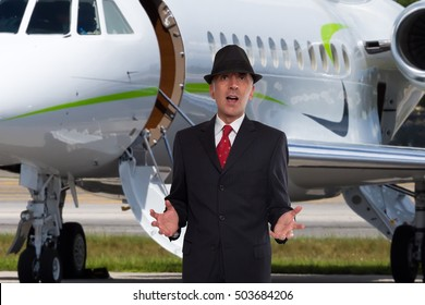 Handsome business man near the steps of a private jet wearing a hat.