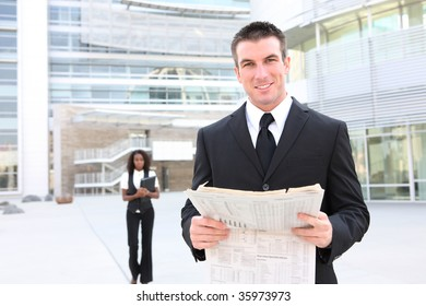 Handsome business man at the office reading a newspaper