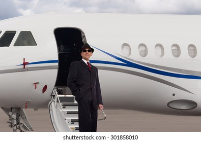 Handsome business man on the steps of a private jet