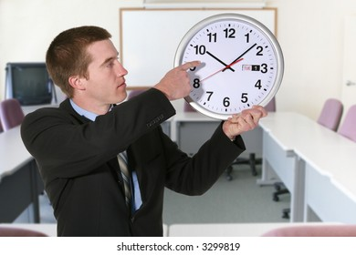 A handsome business man pointing to a clock in the office