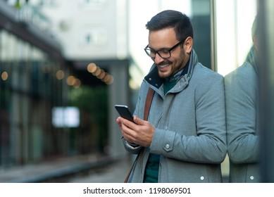 Handsome business man sending message