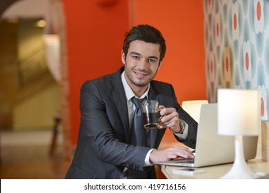 Handsome business man sitting in restaurant talking on the phone and working on his laptop