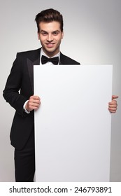 Handsome business man smiling at the camera while holding an empty board.