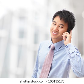 handsome business man speaking mobile phone at his company office building, model is a asian male