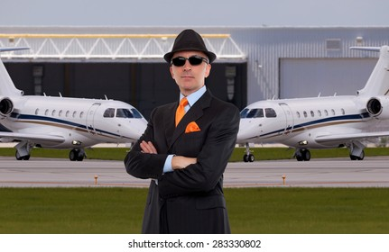 Handsome business man standing in front of private jets