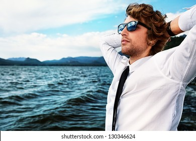 Handsome business man standing on a seaside and looking into the distance.