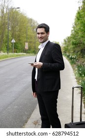 Handsome business man standing on a highway and catching a car