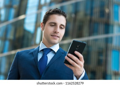 Handsome business man in suit texting message in front od modern building