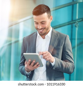 Handsome business man using his tablet, lens flare effect
