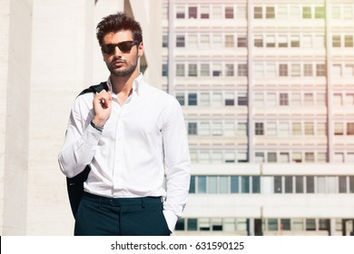 Handsome business man is walking in the city. With sunglasses and white shirt. The boy holds a suit jacket over his shoulder. Behind him, a modern building with windows of offices.
