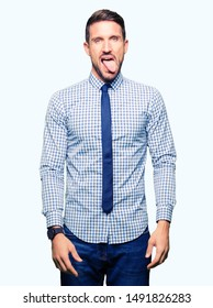 Handsome business man wearing tie sticking tongue out happy with funny expression. Emotion concept.
