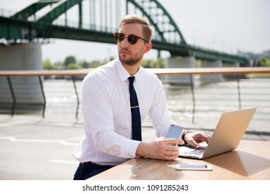 Handsome business man working on laptop outdoor