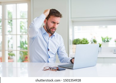 Handsome business man working using computer laptop stressed with hand on head, shocked with shame and surprise face, angry and frustrated. Fear and upset for mistake.