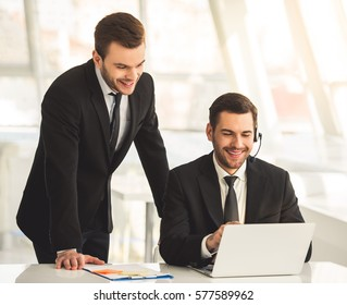 Handsome business partners in suit and are using a laptop, talking and smiling while working in office