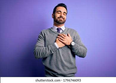 Handsome businessman with beard wearing casual tie standing over purple background smiling with hands on chest with closed eyes and grateful gesture on face. Health concept.