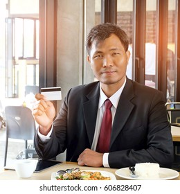 Handsome businessman in black suit show credit card after order food for lunch.