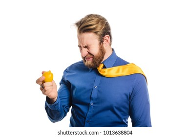 Handsome businessman in a blue business suit standing isolated against white background eats a lemon and wrinkled from sour