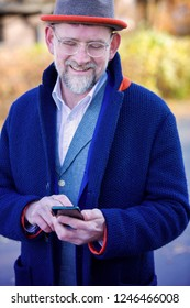 handsome businessman in blue coat standing outside and looking at his phone