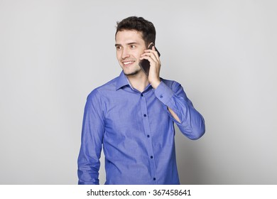 Handsome businessman in blue shirt talking on cellphone.