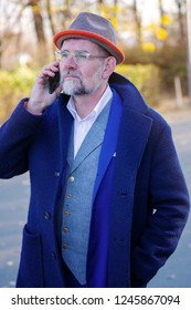 handsome businessman in blue suit standing outside and talking on phone