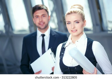 Handsome businessman and businesswoman are discussing new project and smiling. They are standing and looking at camera happily. The man is holding documents. The woman is carrying a blueprint