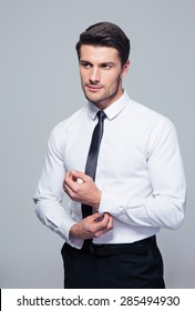 Handsome businessman buttoning shirt over gray background