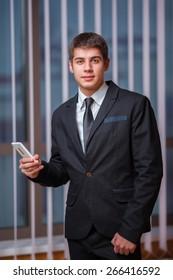 Handsome businessman with cellphone indoor