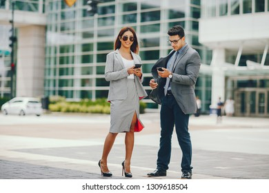 Handsome businessman in a city. Businessman in a glasses. Business couple in a summer city. Man and woman standing with phone. Pretty girl in a dress with her parther.