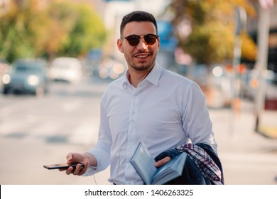 Handsome businessman is in the city, talking and walking on the street, holding notebook in his hands, calling for a taxi ride, e-hailing